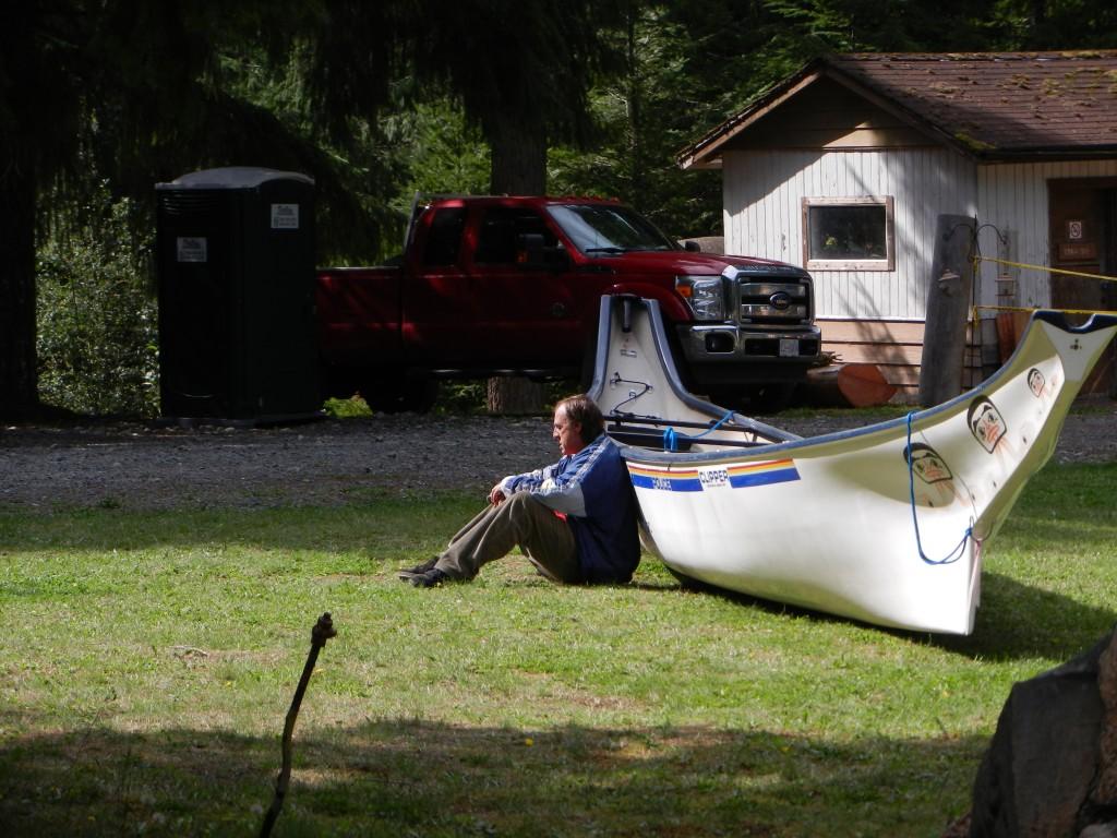 man in blue jacket by canoe